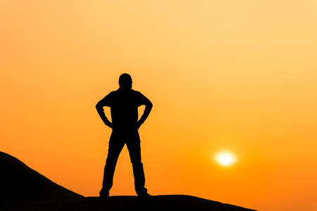 Silhouette of woman is standing and enjoy sunrise view.