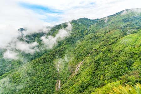 green ridge: Small waterfall on green mountain ridge in rain forest on cloudy day.