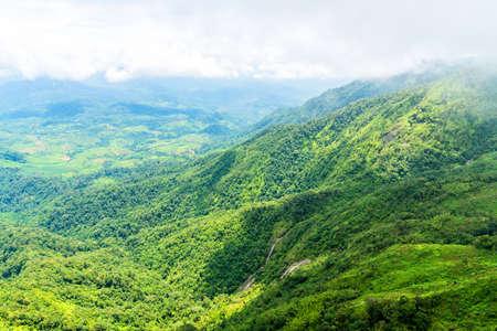 green ridge: Aerial view of waterfall in green mountain ridge in rain forest on cloudy day. Stock Photo