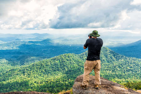 valley view: Male photographer enjoying and taking top view valley rain forest photo from mountain cliff.