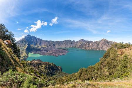 crater lake: Panorama landscape of active volcano Baru Jari, Lake Segara Anak and summit of Rinjani mountain. Lombok island, Indonesia. Stock Photo