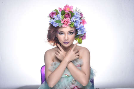 nonchalant: Studio shot of a good looking young woman wearing white attire and a crown of faux flowers on her head. Stock Photo
