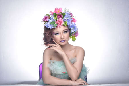 faux: Studio shot of a good looking young woman wearing white attire and a crown of faux flowers on her head. Stock Photo