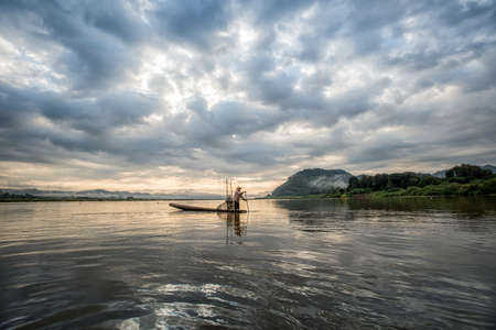 tradional: Fisherman on boat in action when fishing of fish trap on Mekong river