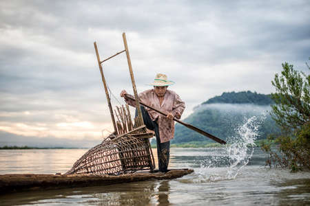 mekong river: Fisherman on boat in action when fishing of fish trap on Mekong river