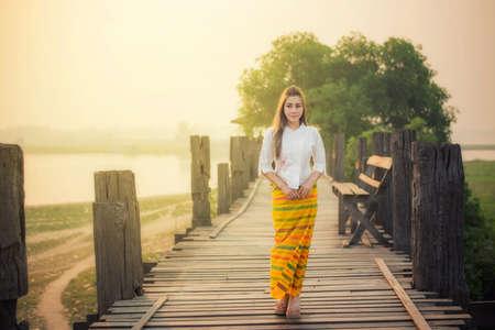 Beautiful girl in Mamdalay Myanmar traditional costume, Burmese woman holding traditional red umbrella and walking on U-Bein Bridge