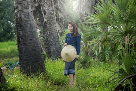 politely: Thai Farmer woman wearing typical Thai dress, on Rice fields background, identity culture of Thailand