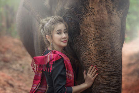Beautiful Asian Woman wears thai dress with her elephant. Closeup portrait of a beautiful girl with elephant.