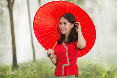 Beautiful Thai girl in Lanna traditional costume with red umbrella. Lanna culture in Northern Thailand