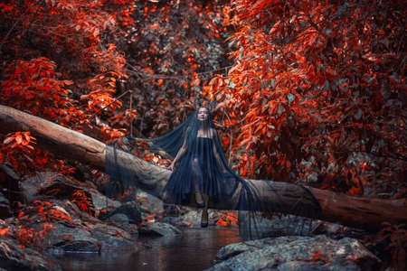 sneaks: Model girl in a black dress and butterfly, dark evil ,queen sneaks through the stone canyon, white, wild ,Princess , vampire , hip toning , creative color,dark boho Stock Photo