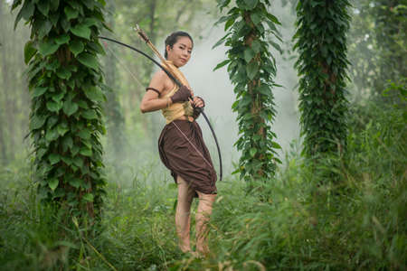 recurve: Beautiful Thai woman archer with longbow and arrows in forest background vintage style at Thailand Stock Photo