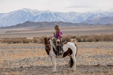 Beautiful Mongolian girl traditionally wearing typical Mongolian Fox dress culture of Mongolia  she Rider horse in Altai Mountain background  at Bayan UlGII, MONGOLIA