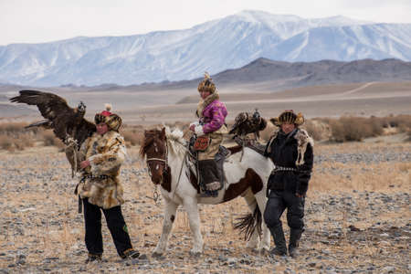 Kazakh Eagle Hunters in traditionally wearing typical Mongolian dress culture of Mongolia she Rider horse on Altai Mountain background  at Bayan UlGII, MONGOLIA Editöryel