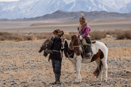 tradition: Kazakh Eagle Hunters in traditionally wearing typical Mongolian dress culture of Mongolia she Rider horse on Altai Mountain background  at Bayan UlGII, MONGOLIA Editorial