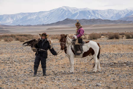 lejano oriente: Kazakh Eagle Hunters in traditionally wearing typical Mongolian dress culture of Mongolia she Rider horse on Altai Mountain background  at Bayan UlGII, MONGOLIA Editorial