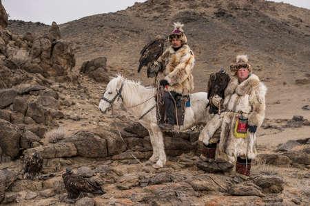 mongolia horse: Thailand tourist in Mongolia traditionally riding horse with Kazakh Eagle Hunter in a desert mountain. Ol-gei,Western Mongolia.