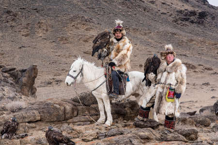 tradition: Thailand tourist in Mongolia traditionally riding horse with Kazakh Eagle Hunter in a desert mountain. Ol-gei,Western Mongolia.