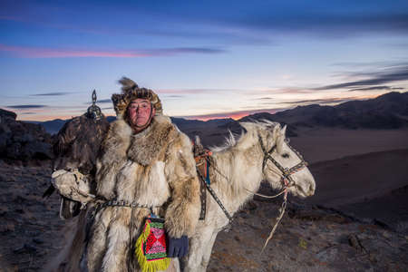 Mongolian Eagle hunter in traditional clothing, holding a golden eagle on his arm and Rider horse on Altai Mountain background at Ba-yan UlGII, MONGOLIA Stock Photo