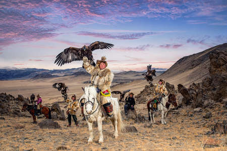 Kazakh Eagle Hunter in traditionally trained golden eagles riding horse in a desert mountain. Olgei,Western Mongolia. Stock Photo