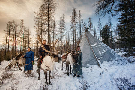 Beautiful portrait of Mongolian Reindeer in traditionally Tsaatan family on their reindeers at Taiga, Mongolia