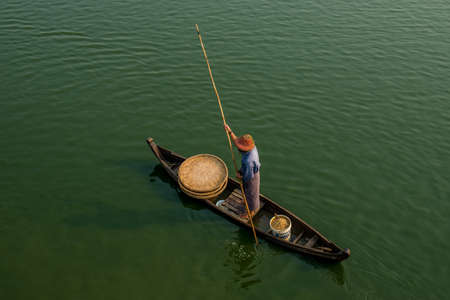 Unidentified people fish in a lake in Amarapura, Myanmar. Amarapura is famed for the longest teak bridge in the world.U Bein bridge in the city of Myanmar. Stock Photo