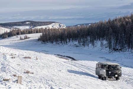 UAZ - Van ruso en la pradera con montañas nevadas en el fondo en Mongolia Foto de archivo