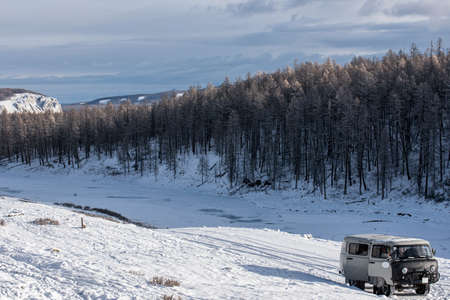 UAZ - Russian Van in prairie with snow-capped mountains on background at Mongolia
