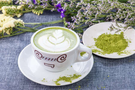 reen tea  Matcha latte in a cup with matcha powder on the wooden table