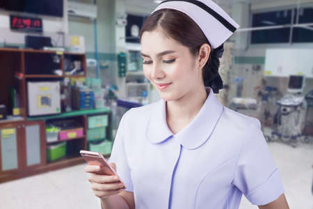 Smiling medical doctor woman with stethoscope. Emergency room background, Thailand