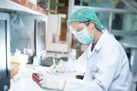Portrait of a female researcher working in a lab scientist using microscope with colleague working in background