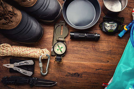 Outdoor travel equipment planning for a mountain trekking camping trip on wooden background. Top view - vintage film grain filter effect styles 版權商用圖片