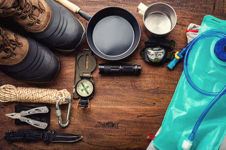 Outdoor travel equipment planning for a mountain trekking camping trip on wooden background. Top view - vintage film grain filter effect styles 写真素材