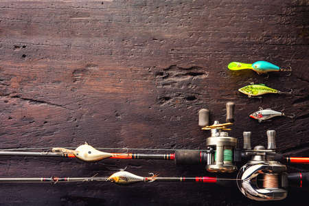 Fishing lures, hooks and accessories on darken wooden background.Top view