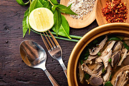 Hot vegetable soup with chicken, puree, herbs, pumpkin seeds for lunch fillet in a bowl over dark rustic wooden background Top view