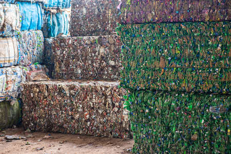 Portrait of Asian Industrial engineer workers with a pile of plastic bottles at the factory for processing and recycling.