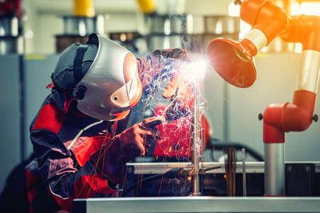 Industrial welder worker is welding metal part in factory with protective mask welding metal. vintage film grain filter effect styles