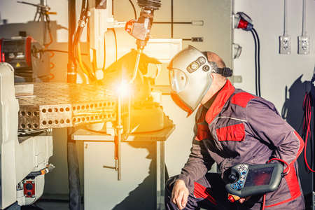 Engineers use remote control of robotic welding on smart factory, industry 4.0 in production line manufacturer factory 版權商用圖片