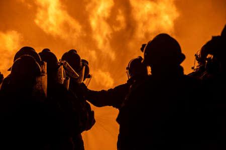 Szkolenie strażaków i ratownictwa. Strażak rozpylający wodę pod wysokim ciśnieniem na ogień Płonący płomień ognia w tle