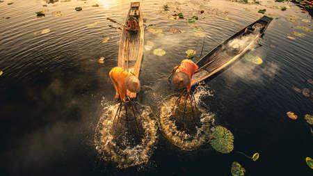 Intha Burmese fishermen on boat catching fish traditional at Inle Lake, Shan State, Myanmar - vintage film grain filter effect styles