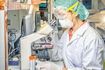 Coronavirus covid 19 epidemic disease with doctor or lab technician scientist holding blood sample tube in laboratory in hospital Thailand