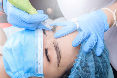 Microblading eyebrows workflow. Permanent makeup for Eyebrows having professional eyebrow tattoo in beauty salon. 스톡 콘텐츠