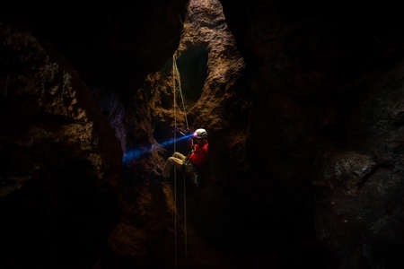 Rescuers or climber descends in a cave fast rope in the dark caves