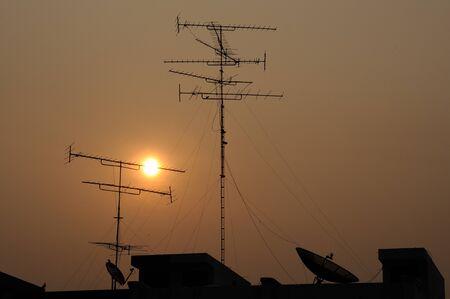 Antenna and satellite dish in sunset  photo