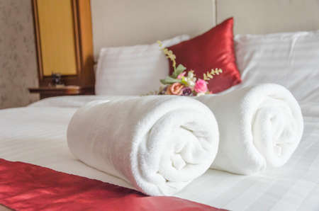 White towel on clean bed,background blured red and white pillows,  summer holiday and vacation concept,selective focus.