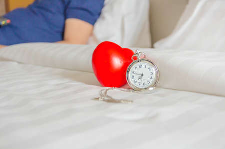Pocket watch and red heart plastic ball on clean bed, summer holiday and vacation concept.