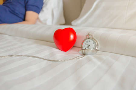 Pocket watach and red heart ball on clean bed, summer holiday ,vacation and health concept.
