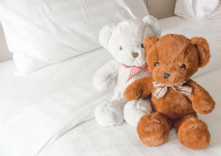 Lovely couple bear sit on white and big bed in bedroom , Clean and white blanket with two pillows,selective focus. Standard-Bild