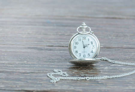 Pocket watch on old wooden background.