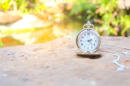 Sliver pocket watch on rock background, time concept.