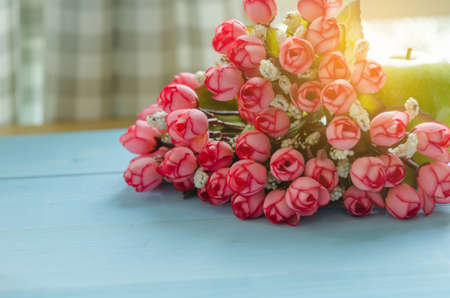 Bouquet of flowers on light blue wooden floor and blur curtain.